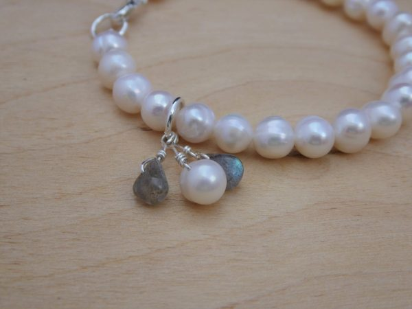 Close up pearl bracelet with charms