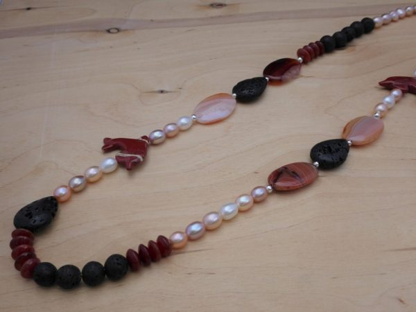Necklace laying flat, cornelian ovals with pear shape Lava beads.